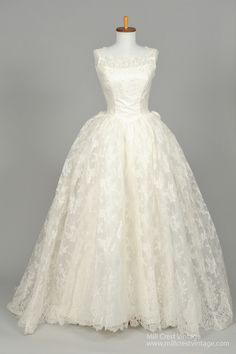 Designed in the 50's, this gorgeous vintage wedding gown is done in a sheer lace embroidered net over an acetate lining in the bodice and a sheer lace embroidered net over a layer of tulle, a lining o