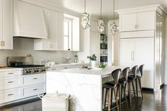 Three glass and brass light pendants hang above a white island finished with a honed white marble waterfall countertop seating four Cherner Counter Stools on a dark stained herringbone wood floor.