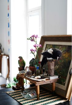 A display of personal items, flowers, and picture in Nor's eclectic home