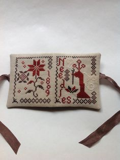 This is a cross stitched needle book that I stitched on a tea color linen with muted overdyed threads. It is a design from Blackbird Designs.