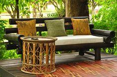 Banco de madeira escura, mesa lateral de bambu, tapete cores quentes. Varanda confortável.