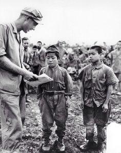Amerykański żołnierz próbuje coś wyjaśnić jeńcom japońskim, czerwiec, 1945 rok. Japończyk po lewej twierdził, że ma 18 lat, ten po prawej - 20
