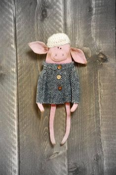 This little piggy has been sewn of 100% cotton and filled with polyester fiber fill. She has been painted with acrylics. She has beads for eyes. She has a loop behind for hanging. She is wearing a grey wool coat and a tiny hand crocheted wool hat. Her clothes are not removable.