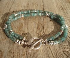 I made this bracelet with two strands, each with a mix of rustic apatite heishi beads and various sterling silver beads. The clasp is made of fine
