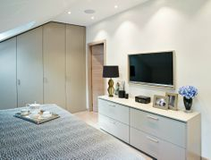 The bespoke built-in wardrobe follows the slope of the roof to elegantly maximise storage space