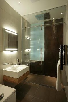Walk in shower enclosure with rainfall shower head and sculptured glass feature