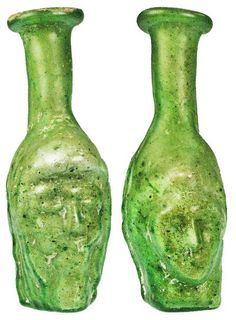 Roman artifacts glass Bottle : Green mold-blown glass bottle, one side with the face of a bearded man, the other with a young boy's face, rolled rim, iridescence and encrustation. 50 - 100 AD