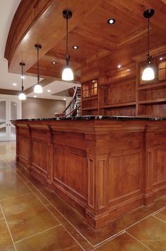 The beautiful wood color choice and countertops in this basement bar are stunning.