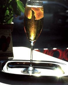 The Daisy Buchanan Recipe   1 ounce Calvados 1/2 ounce pear liqueur Champagne Wide strip of lemon peel, for garnish