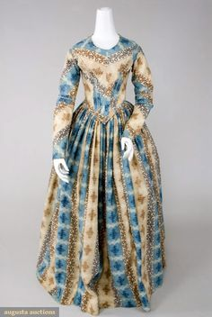 BLUE & BROWN WOOL DRESS & PELERINE, 1840s  Go Back        Lot: 28      November, 2007 -Tasha Tudor Historic Costume Collection      New Hope, PA    Fine cream wool tabby, printed with stripes of blue and beige with interlacing scrolls, trimmed with cream braid on self fabric bands, piped collarless neckline, fitted bodice, center front point at waist, piped seams, panel curving from waist point outward to shoulders, fitted sleeves with bands of fabric above elbows, bodice boned and lined…