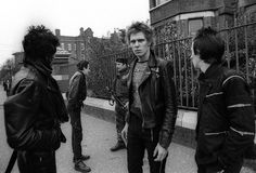 "The Clash photographed in October 1977 in Belfast by Adrian Boot, after their gig at Belfasts Ulster Hall got cancelled, officially because of insurance problems but with rumours suggesting that Joe Strummer had received a death threat. The cancellation resulted in heavy handed police enforcement which left the disappointed fans and the band angry, sad, confused and helpless.   ""…So instead of a sound check I was to do a photo-session with the Clash, a simple walk about, black and white…"