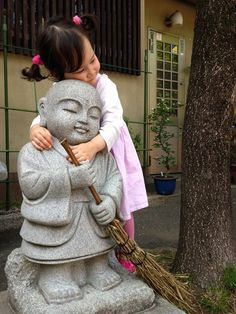 Little Japanese girl hugging a sweeping Jizo