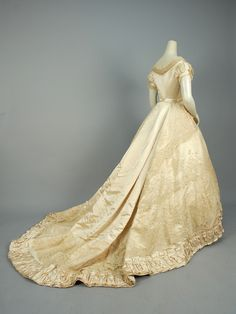 "PARIS LABEL SILK and LACE WEDDING DRESS, 1866. 2-piece ivory satin decorated with swags of lace on net, short sleeve bodice having self buttons and pleated tulle trim, trained skirt with wide pleated hem band. Petersham label ""Mon. Vignon 182. Rue de Rivoli Paris""  - whitakerauction"