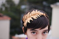 I just recreated this head band out of a bought silk fern (3.95), 2 cans of spray paint (4.99 each), an old hair tie, and a piece of 8 inch ribbon, some thread and a needle.  It looks super cute, and is antique silver in colour.