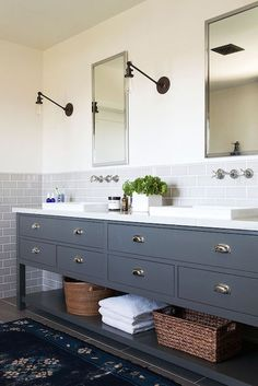 nickel framed medicine cabinets, flanked by sconces, stand over a dark gray vanity which is topped with a pair of shallow vessel sinks set atop a white marble counter with wall mount faucets above mounted on a gray subway tiled half wall backsplash