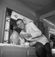 Frank Sinatra putting moves on a doughnut. In his trailer during a break in filming, circa 1950.