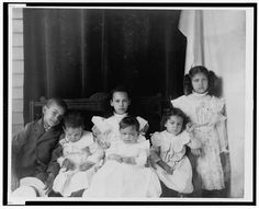 [African American children posed for portrait on a porch]