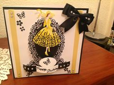 Made by Alison Wing -Used the oval shape die from the flectere range including the mini oval and sentiment and one of my tattered lace ladies and did a black border around white cardstock adding splashes of lemon in the ribbon and used a yellow promarker on the dress hat and shoes. Added a few sparkly beads, bow, butterflies and tiny flowers to complete.