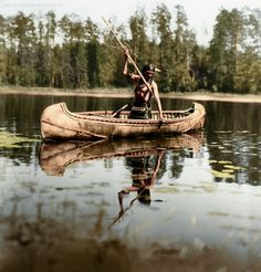 Colorized photo of an Anishinaabe person spearfishing in Minnesota This is so amazing. Having the colorized version really brings this scene to life; it's easier to put it mentally into the lakes I've personally seen up North. That canoe is amazing as well.