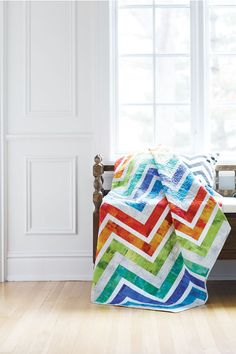 Bring on spring with this bright, energetic quilt. Nancy Mahoney's ingenious design is based on simple log cabin-style blocks. When joined together, they give the illusion of connected strips.