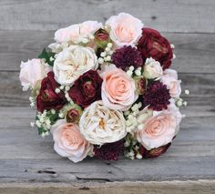 This faux flower bouquet is rich with color, made with peach roses, ivory roses, burgundy ranunculus and babies breath that are silk flowers. See more here: https://www.etsy.com/listing/486422398/wedding-flowers-wedding-bouquet-keepsake