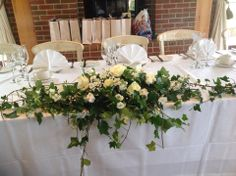 Long and low table arrangement ideal for top table decorated using white roses,lisianthus,stock and gip.Trailing ivy has been used to fill in the arrangement and connect it to another arrangement further along the table.