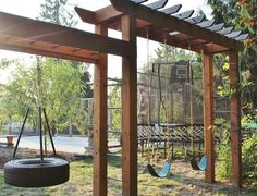 Swing set with arbor-like elements. The landscaping around the family homestead on which this swing set is built is an amazing example of DIY ingenuity in conjunction with help from a landscape designer to formulate the overarching plan.