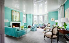 In a Kentucky estate designed by architect Joel Barkley and Todd Klein, the blue striations on the living room's handmade silk wall covering by Gracie inspired the rest of the space's palette. Arranged near the fireplace are a sofa in a custom-colored TylerGraphic linen, a Regency armchair in a Pierre Frey solid, and a club chair in a TylerGraphic floral linen; at far right is a pair of green 1960s resin lamps by Silvano Pantani from Swank Lighting.