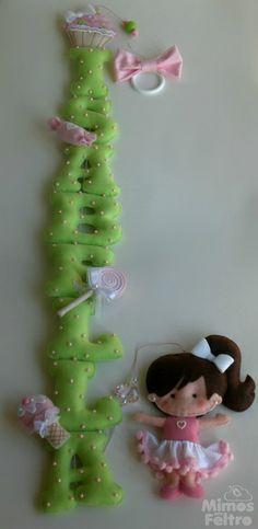 Pingente com o nome da menina, decorado com pedrinhas de acrílico e docinhos em feltro. Na ponta, uma boneca com as características da menina que receberá a peça. Consulte!  *Cada letra mede cerca de 10cm de altura. R$ 80,00