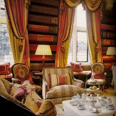 Victorian House Interior With Elegant Curtains And Built In Bookcases.