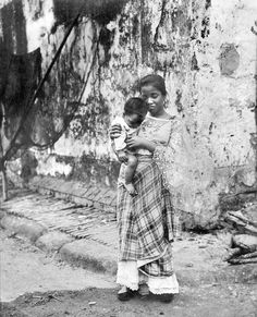 The mother looks sad, I wonder why? That looks like a very old wall or building even for over than 100 years ago. To the left looks like a fish net hanging. Philippines Fashion, Philippines Culture, Filipino Art, Filipino Culture, Filipino Fashion, Filipina Beauty, Ancient Beauty, Historical Pictures, Mother And Child