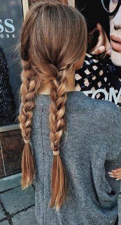 Brown hair with blonde highlights. Pigtail braids.