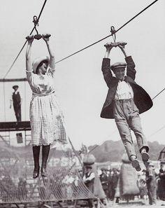 A couple enjoys a zip-line ride, 1920's