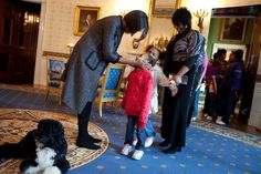 1/20/2010 First Lady Michelle Obama greets a young visitor touring the White House during a surprise visit in the Blue Room with family dog Bo on the anniversary of the inauguration.''