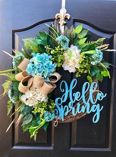Gorgeous Year Round Door Wreath! This gorgeous spring wreath is perfect for greeting your guests to your home, with this one of a kind door wreath. Made up on an 18 grapevine wreath with moss, mixed flowing greenery of ivies, ferns and ficus leaves. Beautiful cream and teal hydrangeas