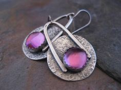 Sterling Silver disk that has been texturized, oxidized and polished. The cabochon is a lab created pink sapphire. These earrings measure slightly
