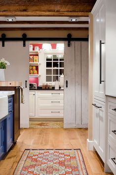 Full-size  pantry with counters and workzone hidden behind sliding barn-style doors