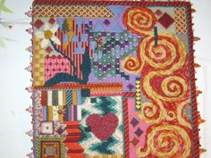A tapestry kit modified by Victoria Sowter then mounted on polystyrene with pinned on beads around the edge.