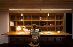 Paulownia wood lines the ceiling of the space, while the floor is hardwood, matching the rest of the loft. Veneered plywood was used to build the cubby-like shelves and desks.