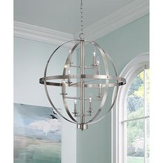 A modern look with eight lights on a frame set within an circular orb style chandelier.