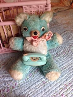 Vintage teddy bear with vintage princess phone.
