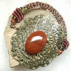 2 tone natural brass and burgundy flat panel viking knit bracelet with burgundy spiral end caps, red tigers eye beads, and a brass filigree closure with a carnelian stone in the center. Knit Bracelet, Bracelets, Viking Knit, Red Tigers Eye, Tiger Eye Beads, Viking Jewelry, Carnelian, Filigree