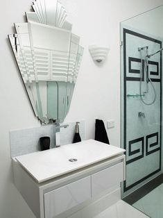 1. Glossy black and silver colors.   2. Symmetry with the mirror and drawers.   3. The mirror, counter, drawers and shower are all geometrical.  #homedecor #homedesign #decorationideas #homeinteriordesign