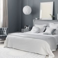 Serene Bedroom    The shades of grey and white seen here are gentle on the senses, the bed is wide enough to collapse on and relax, and the bedside radio is a personal touch your guests will appreciate.    Headboard fabric - Mark Alexander  Similar radio - John Lewis   Paint - Farrow & Ball    Photograph by Polly Wreford