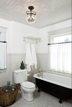marble hex tile floor, black and white clawfoot tub, gray wainscoting and paneled ceiling