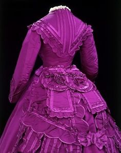 """Designers: Vignon    Materials: Ribbed silk trimmed with satin, faced with cotton, brass    From V & A Museum:  Period:1869-1870 (made)    Paris      """"Vivid magenta-coloured silk gives this dress a rich and flamboyant appearance. It was probably dyed with one of the new synthetic colours produced from the late 1850s onwards, although intense hues could also be created using natural dyes. The artificial forms of magenta were very popular and a battle for patents began as dyers sought to…"""