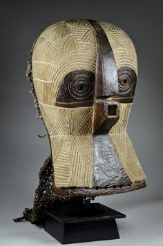 Luba Kifwebe owl mask. Ethnic group: Luba, Songye Country of origin : D. R. Congo Material : Wood, pigment, paint, raffia, textile, shells Approximate age : Mid 20th Century  Dimensions: 49cm x 28cm x 22cm (wooden part) + raffia, textile