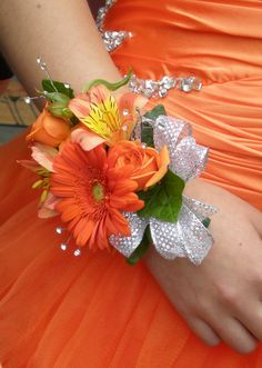 Wrist corsage with orange alstromeria and gerbera daisy with silver