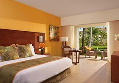 The Caribbean-inspired Deluxe Guestrooms with a tropical view at Now Larimar feature lush tropical gardens beyond the terrace.