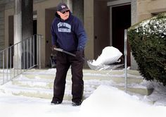 George Greenland with Casiello Construction and Property Management in Wildwood Crest clears the steps of the church before salting the area.